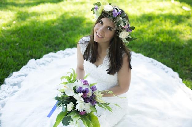 Bella giovane sposa in una corona con un mazzo di fiori in mano