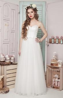 Bella giovane sposa nella decorazione romantica di nozze rosa e verde. bottiglie di scatole di legno e diverse decorazioni di nozze