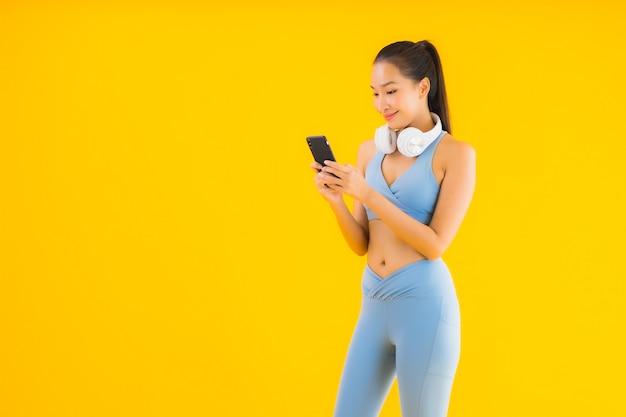 Bella giovane usura asiatica di sport di usura della donna del ritratto con lo smart phone