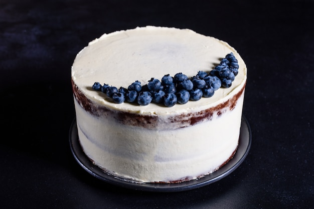 Bella gustosa torta con crema bianca e bacche di mirtillo