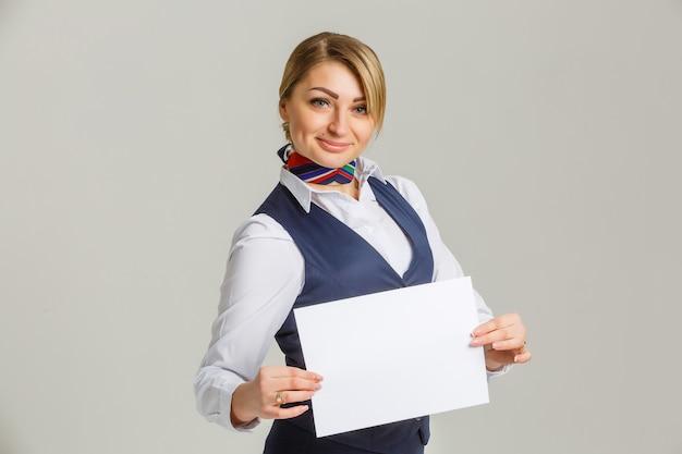 Bella hostess con un pezzo di carta bianca tra le mani