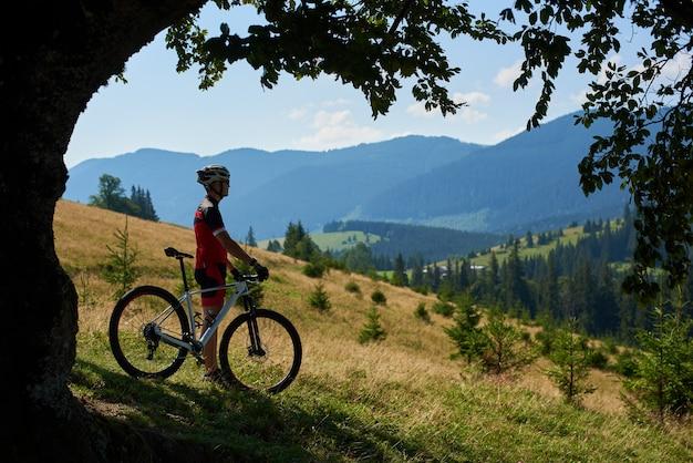 Bella immagine di giovani motociclisti coppia, uomo e donna in piedi con le bici sulla collina erbosa, godendo di una fantastica vista della magnifica catena montuosa blu nella cornice ovale del grande ramo di un albero verde.