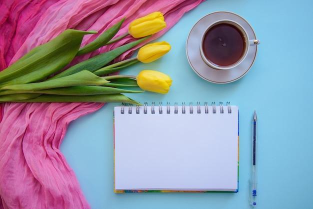 Bella immagine romantica con blocco note, tè e tulipani su sfondo blu