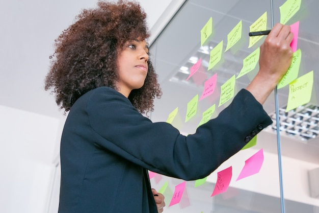 Bella imprenditrice di successo scrivendo su adesivo con pennarello. responsabile femminile riccio fiducioso premuroso che condivide l'idea per il progetto e che prende nota. brainstorming, business e concetto di formazione