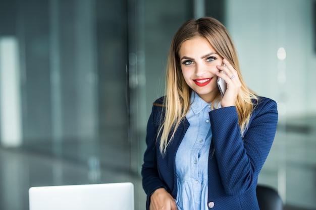 Bella imprenditrice impegnata, in piedi in ufficio, scrivendo nel pianificatore e parlando al telefono cellulare.