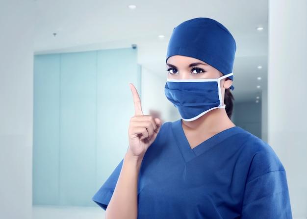 Bella infermiera asiatica con maschera medica che punta la mano