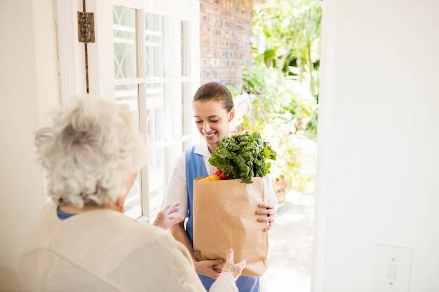 Bella infermiera che porta le verdure al paziente anziano a casa