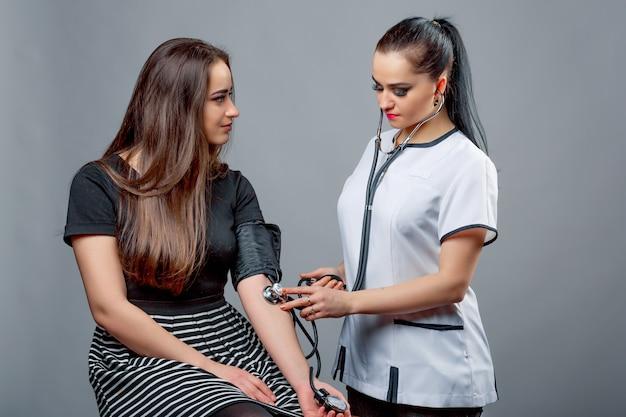 Bella infermiera sta prendendo la pressione sanguigna della paziente