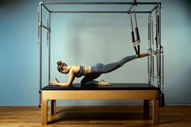 Bella istruttore di fitness sottile su sfondo grigio riformatore.