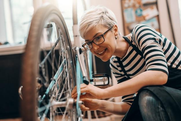 Bella lavoratrice caucasica con capelli biondi corti e occhiali accovacciati e riparare biciclette. interno officina bici.