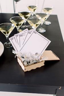 Bella linea di cocktail alcolici in una festa di compleanno al chiuso, tequila, martini, vodka e altri sul tavolo da mazzo decorato per catering, scatola di legno con regali e biglietti augurali