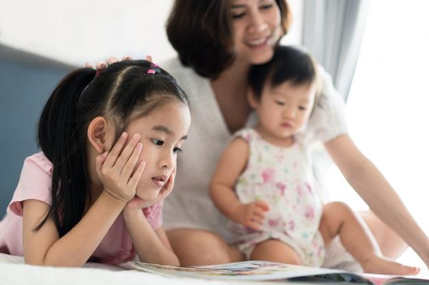 Bella madre asiatica che legge un libro di fiabe con i suoi figli sul letto.