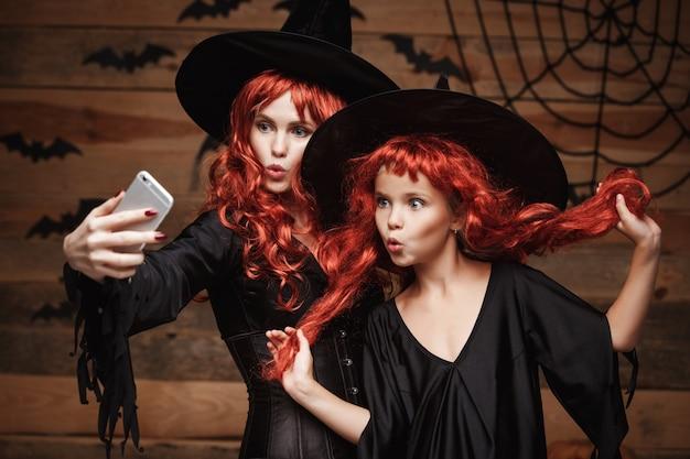 Bella madre caucasica e sua figlia con lunghi capelli rossi in costumi della strega che prendono un selfie