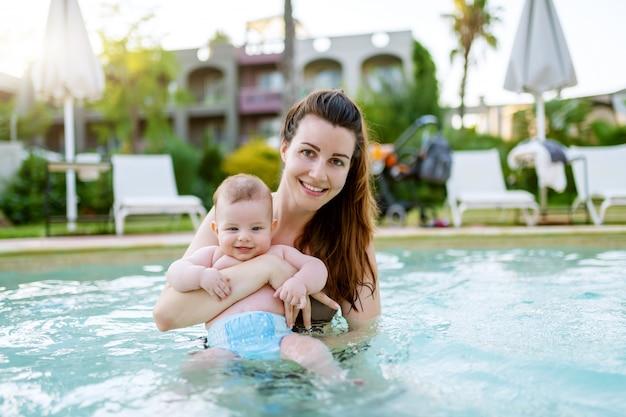 Bella madre caucasica in piedi in piscina e tenendo il suo figlio di 6 mesi. bambino che guarda l'obbiettivo e sorridente.