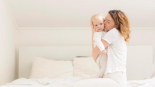 Bella madre che abbraccia la neonata a casa