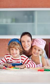 Bella madre che cuoce con i suoi bambini