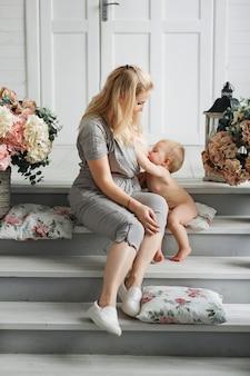 Bella madre con grande seno che allatta al seno il suo bambino mentre si siede sulle scale di legno
