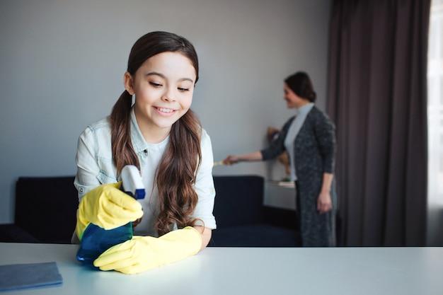Bella madre e figlia caucasiche castane che puliscono insieme nella sala. la ragazza sta di fronte e usa lo spray sul tavolo. indossa guanti protettivi gialli. sua madre è alle spalle.