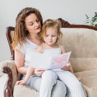 Bella madre e figlia che leggono la cartolina d'auguri di festa della mamma che si siede sul sofà
