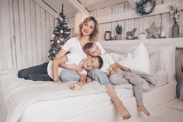 Bella madre e i suoi due bambini che abbracciano in bianco camera da letto in stile scandinavo con albero di natale