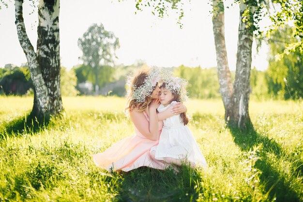 Bella madre felice con una figlia dell'aspetto caucasico che abbraccia nel prato