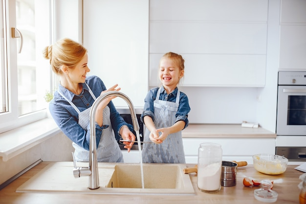 Bella madre in una camicia blu e grembiule sta preparando la cena a casa in cucina