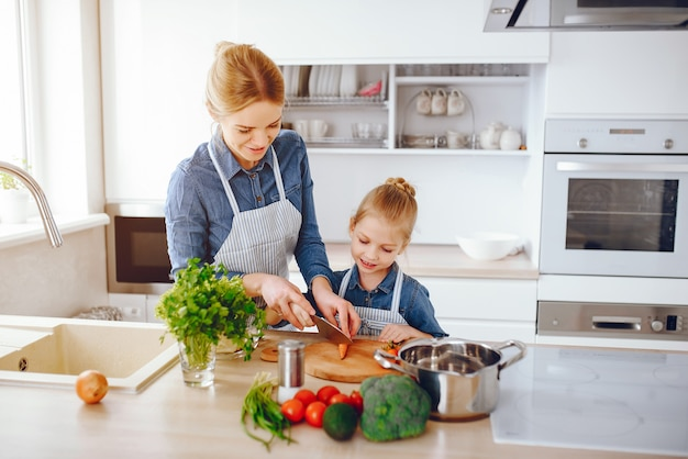 Bella madre in una camicia blu e grembiule sta preparando un'insalata di verdure fresche a casa