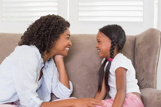 Bella madre seduta sul divano con sua figlia