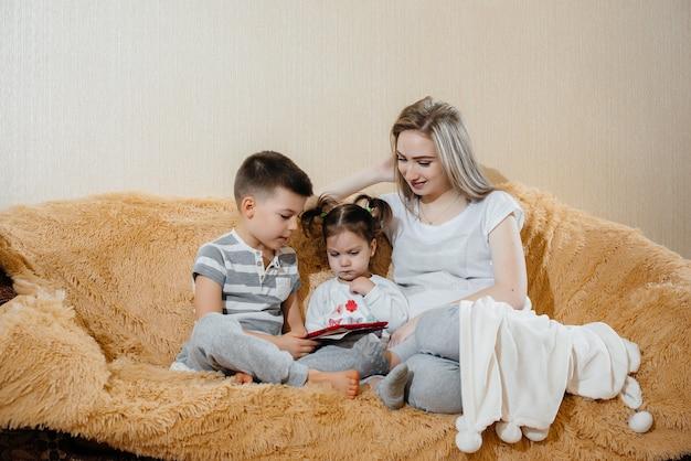 Bella mamma incinta seduta sul divano con suo figlio e figlia e giocando tablet.