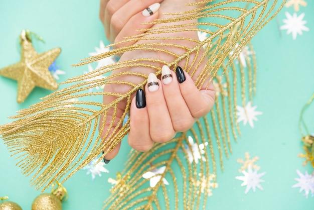 Bella manicure femminile su verde con un elemento festivo.