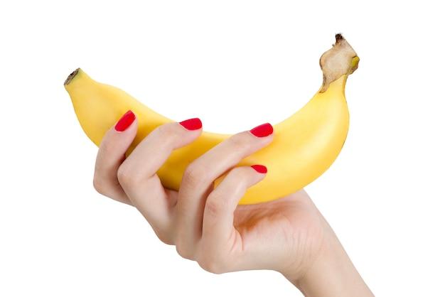 Bella mano della donna con la banana rossa della tenuta dell'unghia isolata su fondo bianco