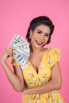 Bella mano della donna di modo felice che tiene i soldi del dollaro