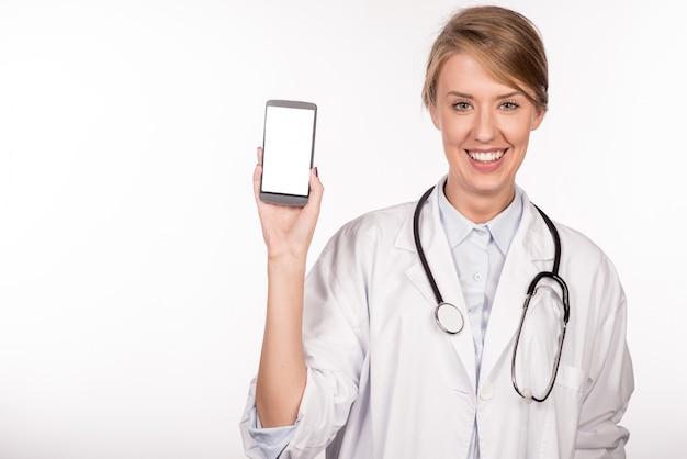 Bella medico femminile sorridente e mostrando un telefono astuto in bianco