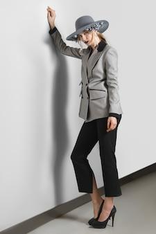Bella modella in giacca, pantaloni e cappello a tesa larga con fiori in posa vicino al muro grigio