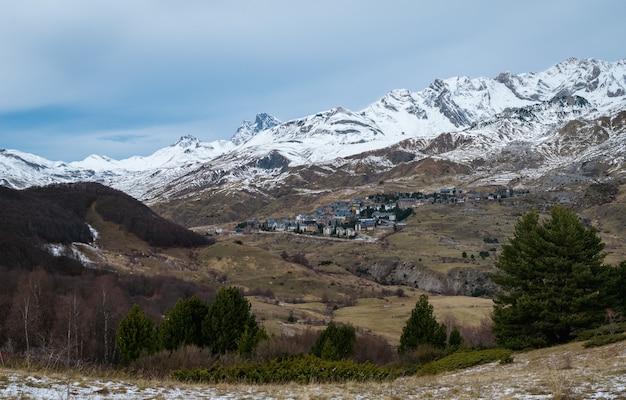 Bella montagna rocciosa ricoperta di neve sotto un cielo nuvoloso