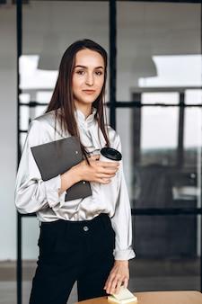 Bella mora con documenti in lei e tazze di caffè, lavorando in ufficio
