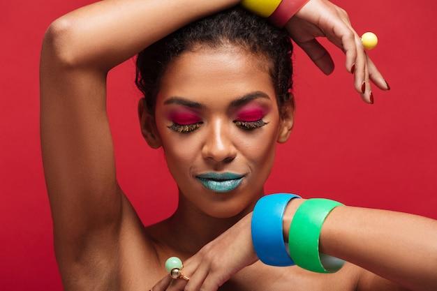 Bella mulatta mezza nuda con il trucco alla moda dimostrando bracciali colorati sulla fotocamera, sul muro rosso
