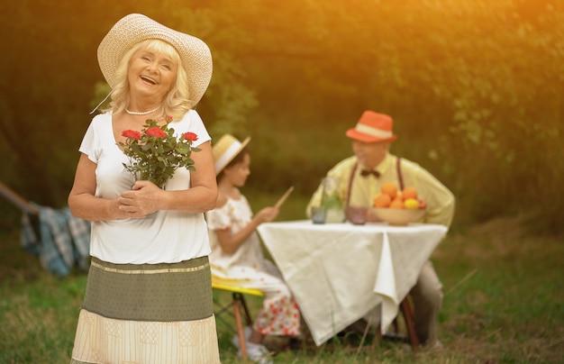 Bella nonna con un mazzo di rose rosse nelle sue mani
