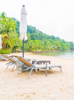 Bella ombrello di lusso silhouette e sedia intorno alla piscina in hotel resort piscina con palme da cocco alle albe tempi - aumentare la lavorazione del colore