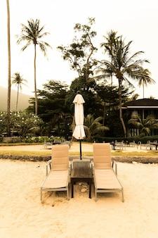 Bella ombrello di lusso silhouette e sedia intorno alla piscina in piscina resort hotel con palme da cocco alle alba tempi - filtro vintage e boost up color processing