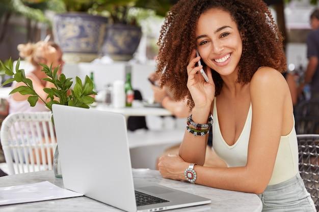 Bella operatore di chiamata femminile dalla pelle scura felice per la ricezione di consulenza, utilizza dispositivi elettronici, riposa in un accogliente bar.