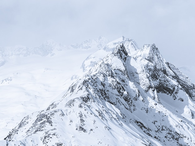 Bella panoramica delle montagne coperte di neve sotto un cielo nebbioso
