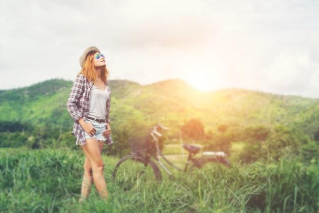 Bella pantaloni a vita bassa donna in piedi su un prato verde con la natura un
