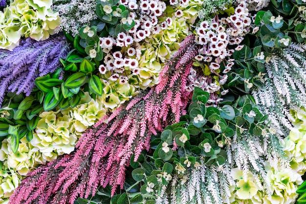 Bella parete di diversi fiori multicolore, foglie verdi, press-wall,