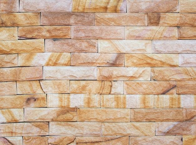 Bella parete di pietra ruvida marrone strutturata e fondo