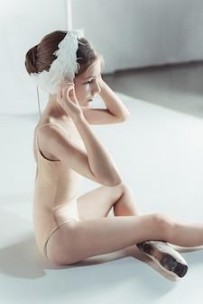 Bella piccola ballerina che indossa una benda di cigno bianco in testa
