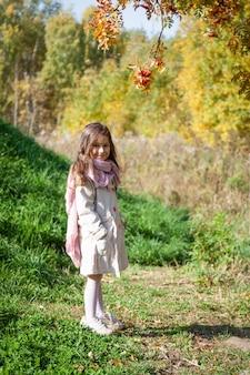 Bella piccola donna il giorno di autunno in foresta