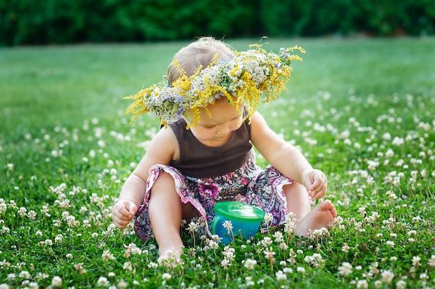 Bella piccola neonata felice in una corona su un prato