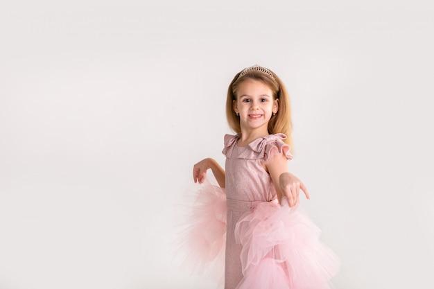 Bella piccola principessa che balla in un lussuoso abito rosa
