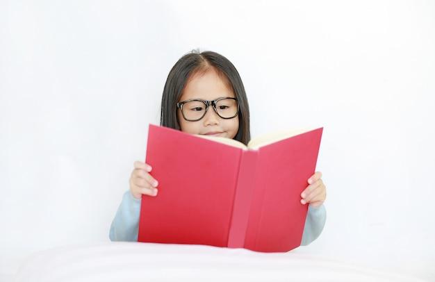 Bella piccola ragazza asiatica felice del bambino che legge libro dalla copertina rigida che si trova sul letto contro il fondo bianco.
